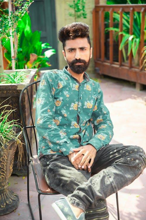 Man Wearing Green Floral Long Sleeves and Black Pants