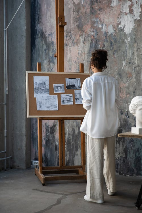 Woman in White Long Sleeves Shirt Looking at Drawings on a Corkboard