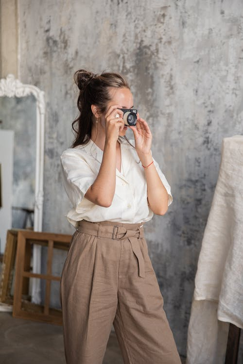 A Woman in White Top and Brown Pants Taking Photos