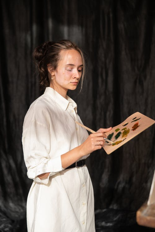 Woman in White Dress Shirt Holding a Paintbrush and Palette