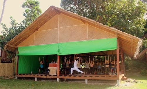 People Practicing Yoga in a Nipa Hut