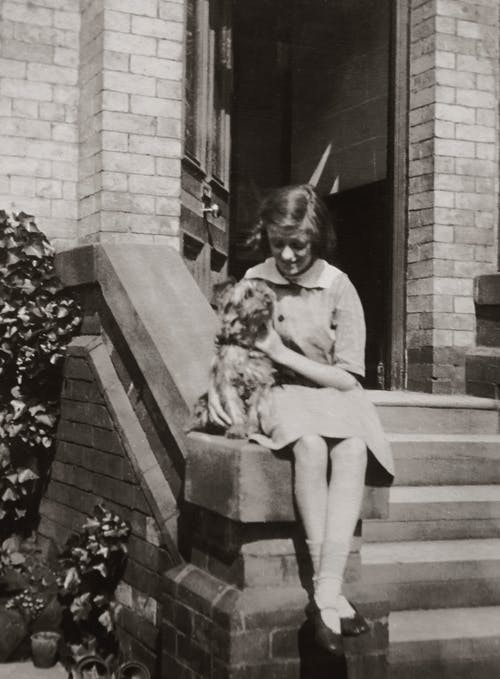 Girl Sitting By the Doorstep With a Dog