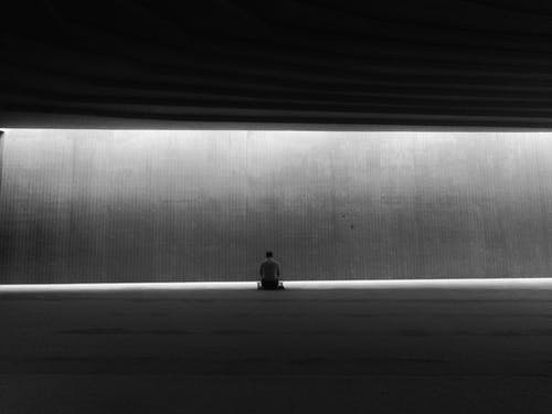 Grayscale Photo of Person Sitting on Floor