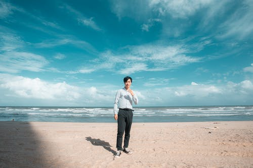 Man in Striped Dress Shirt and Black Pants Standing on Seashore