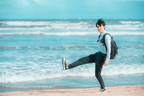Man in White Dress Shirt and Black Pants Carrying Black and White Skateboard on Beach during