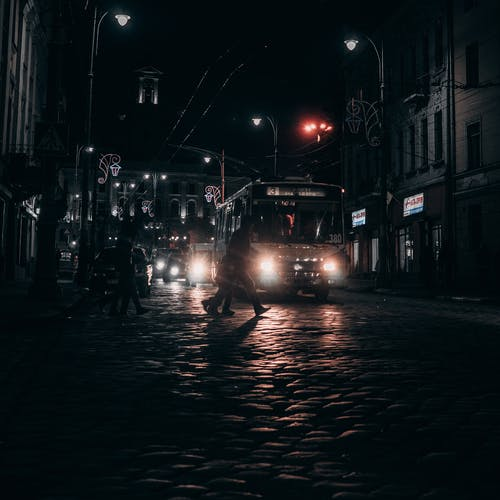 Night road with pedestrians and cars in city
