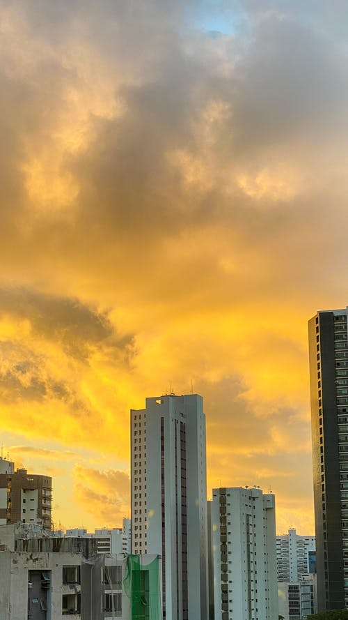 City Skyline Under Orange and Yellow Cloudy Sky during Sunset