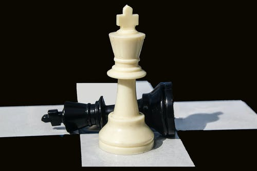 Close-Up View of White and Black Chess Pieces on a Chessboard