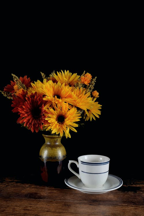 Yellow and Orange Flowers on a Flower Vase Beside a White Cup on a Saucer