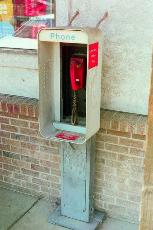 Red Public Telephone Mounted on a Wall