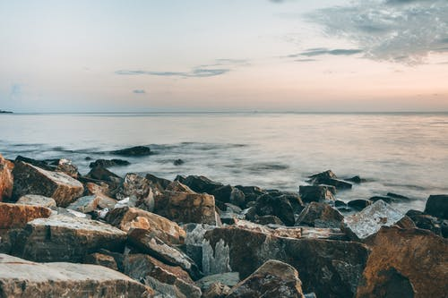 Scenic view of rocky formations on coast against rippled sea with horizon under cloudy sky at sunset