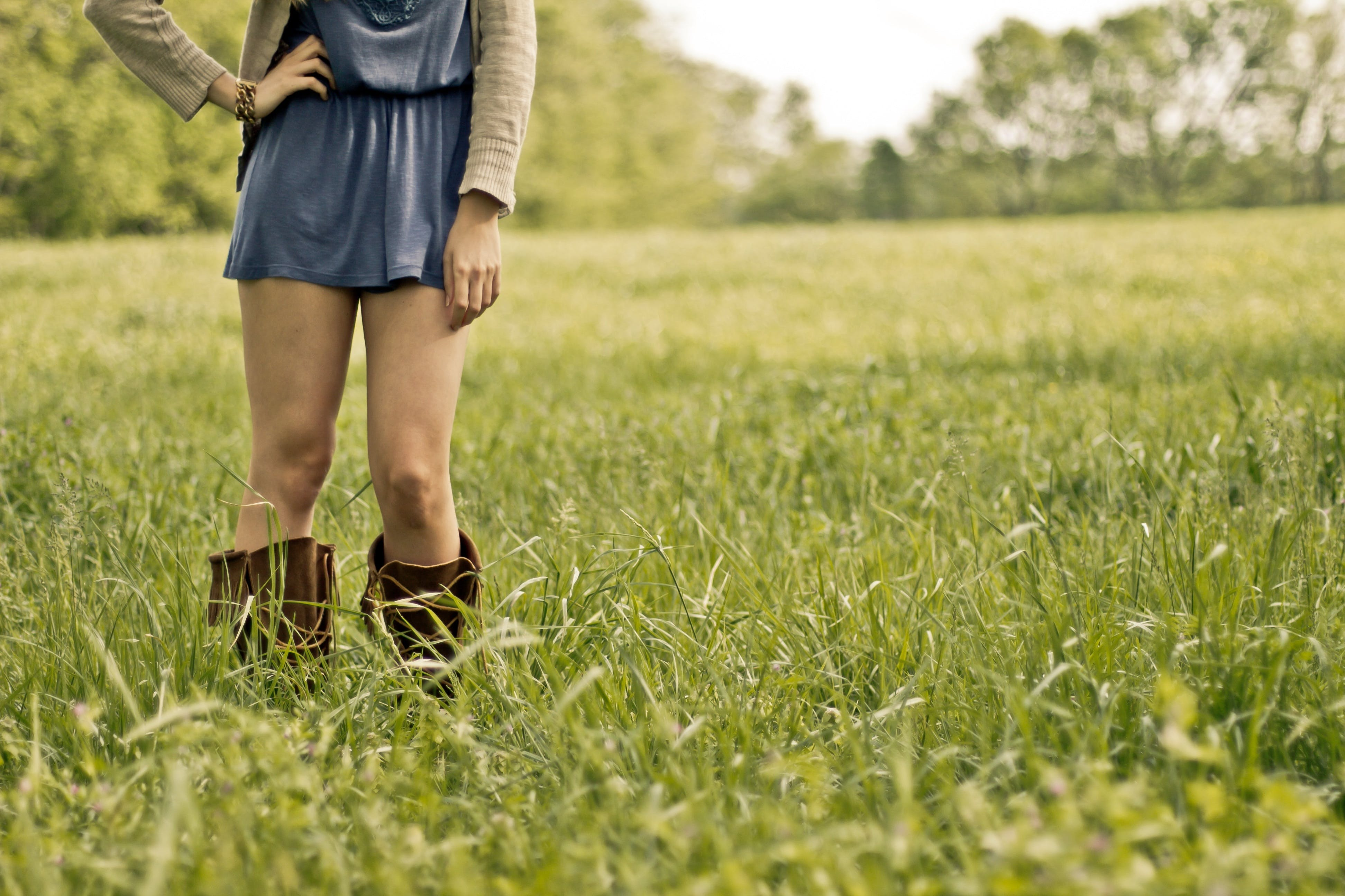 Person Wearing Brown Boots Standing on Green Grass Ground