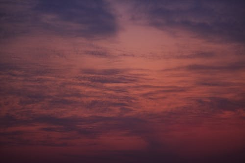 Picturesque scenery of colorful violet sky with clouds at calm sunset in twilight