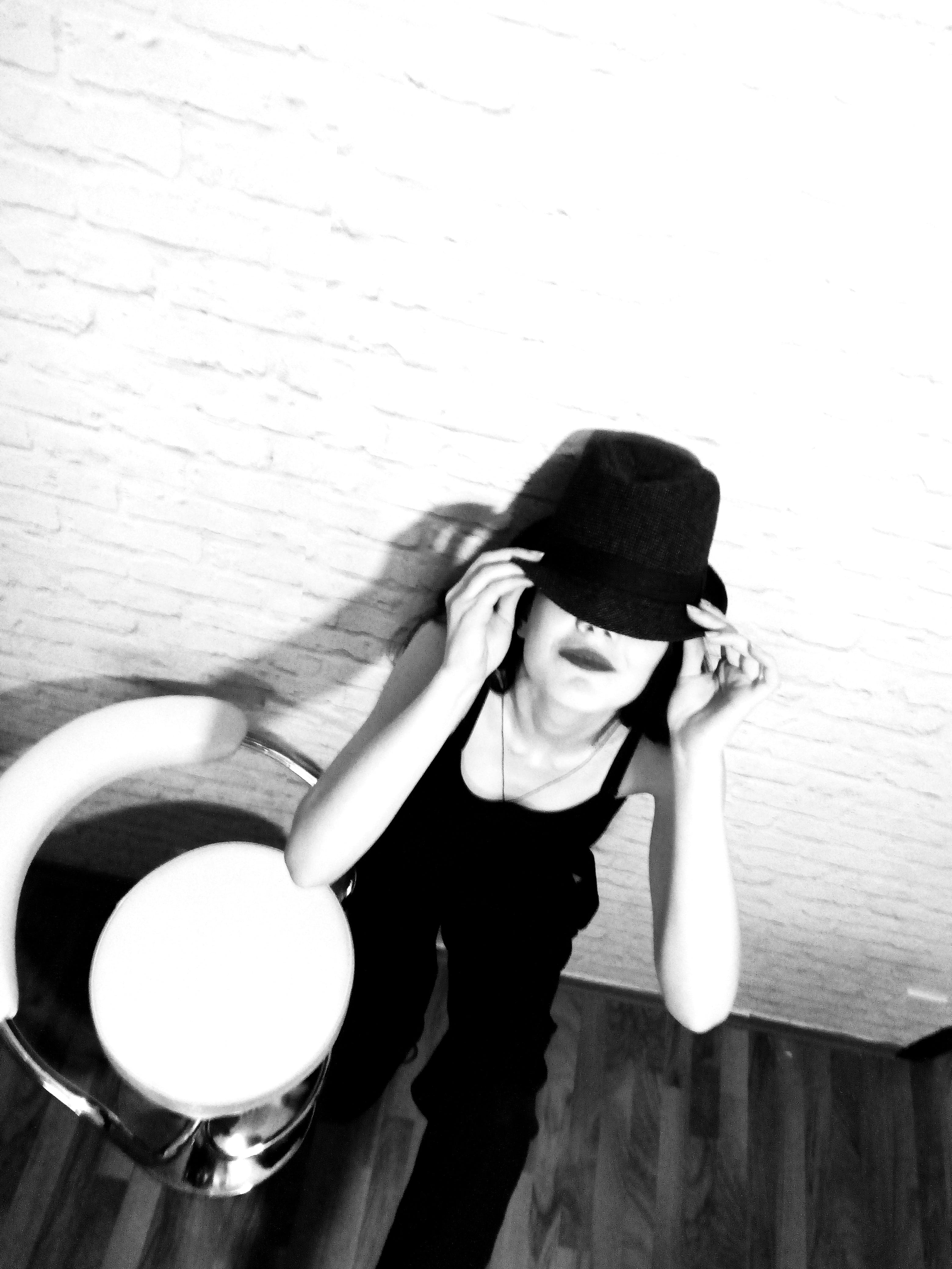 Woman Holding Hat Beside Stool