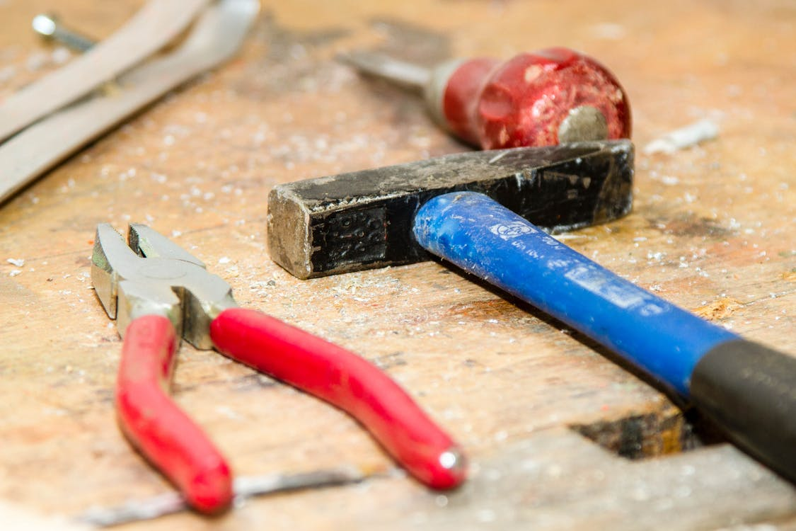 Red and Gray Pliers Beside Blue and Black Hammer