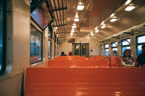 Interior of train wagon with metal shelves ad bright seats with passengers riding