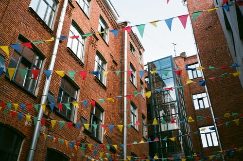 From below of exterior of yard of brick residential building with decorative colorful flags in daytime