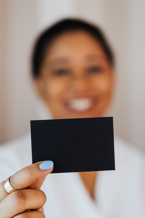 Person Holding a Small Black Paper