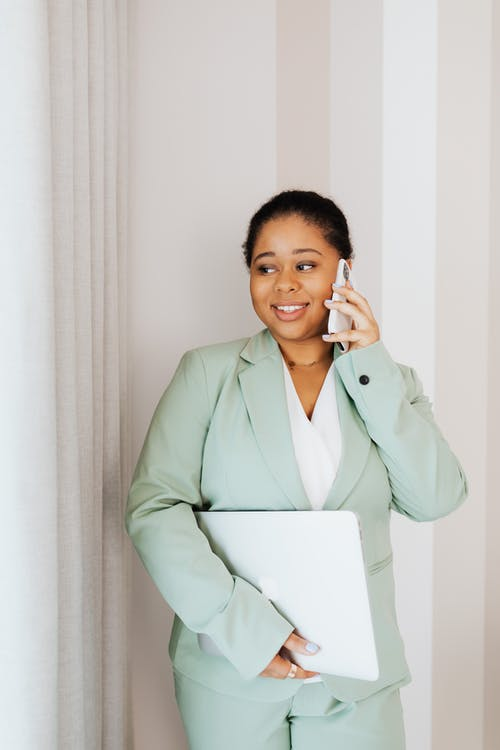 Woman in Light Green Suit Standing while Talking on Cellphone