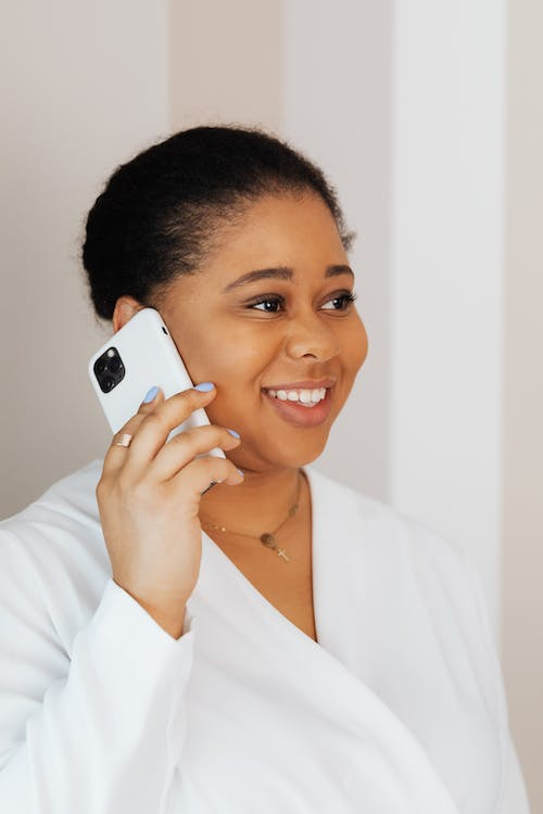 Woman in White Top Smiling while Talking on Cellphone