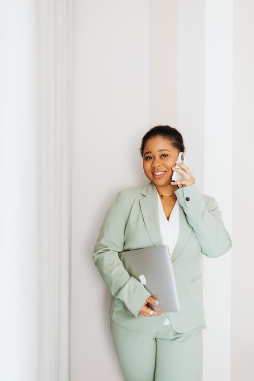 Woman in Green Suit Talking on Cellphone