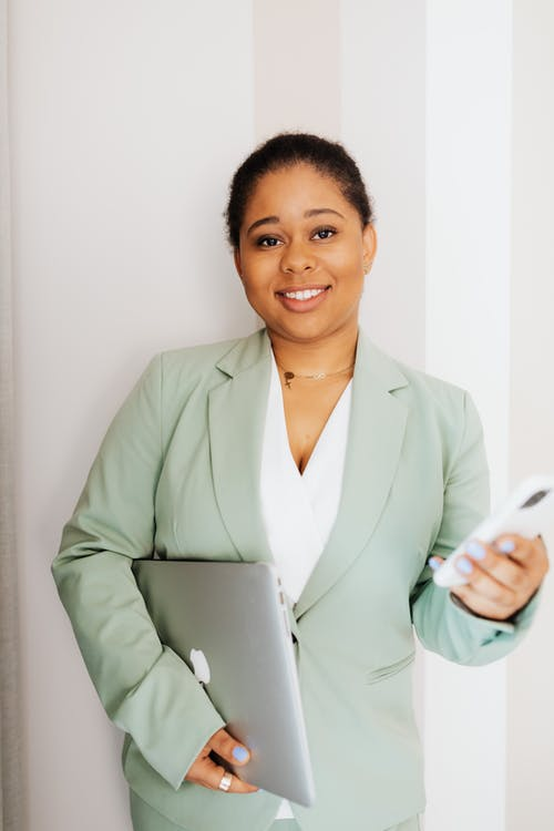 Smiling Woman in Light Green Suit Holding Gadgets