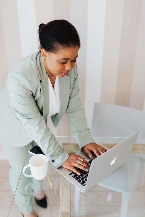 Man in White Suit Using Macbook Pro
