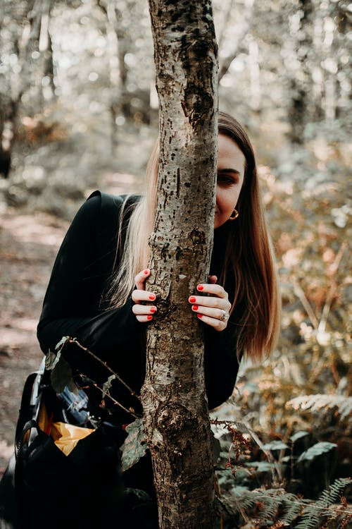 Woman in Black Leather Jacket Leaning on Brown Tree