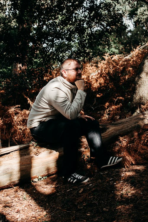 Man in Brown Long Sleeve Shirt and Black Pants Sitting on Brown Wooden Bench