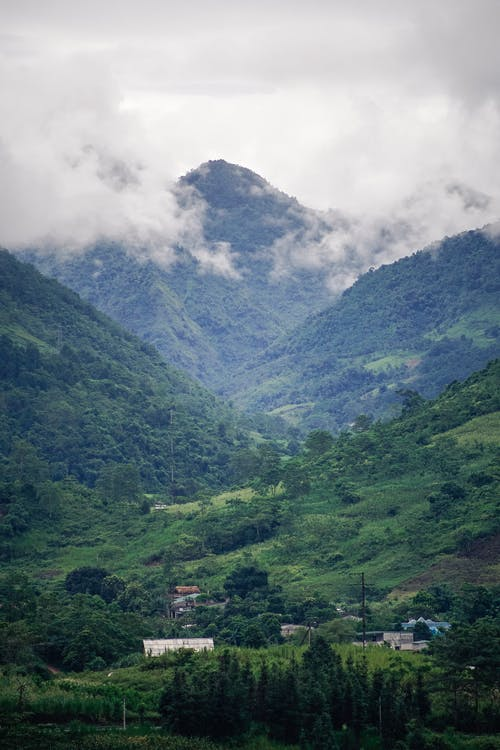 Clouds over picturesque mountains covered with green trees