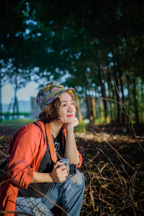 Side view of positive Asian female photographer in casual clothes and hat sitting on dried grass with photo camera in hand in woods with trees on blurred background