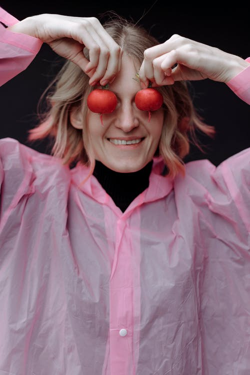 Woman in Pink Raincoat Holding Vegetables Near Her Eyes