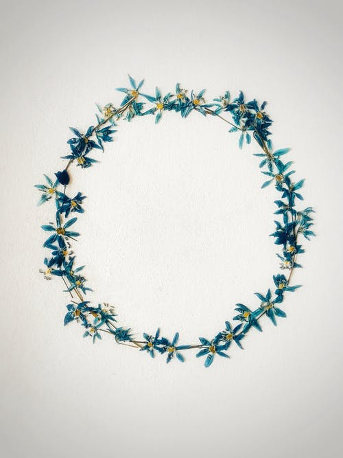 Top view of stylish head wreath made of gentle small blue flowers placed on white table