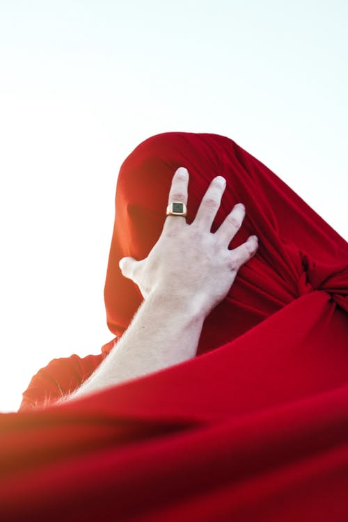 Faceless man covering head with red cloth against blue sky