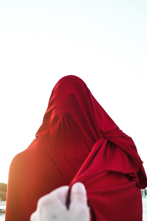 Person pulling red cloth covering unrecognizable person