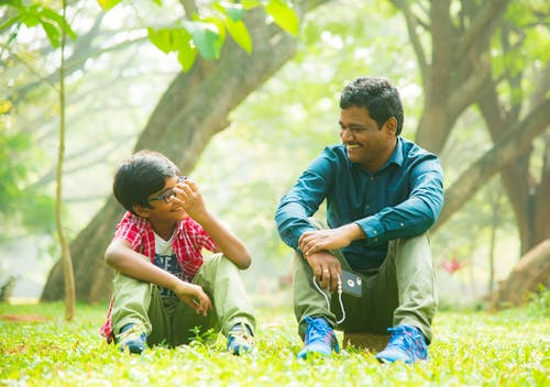 A Man and a Boy Sitting on the Green Grass