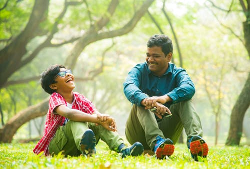 A Man and a Boy Laughing while Sitting on the Gree Grass
