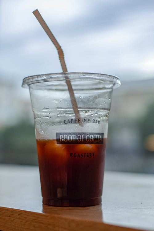Plastic cup with iced tea on wooden table