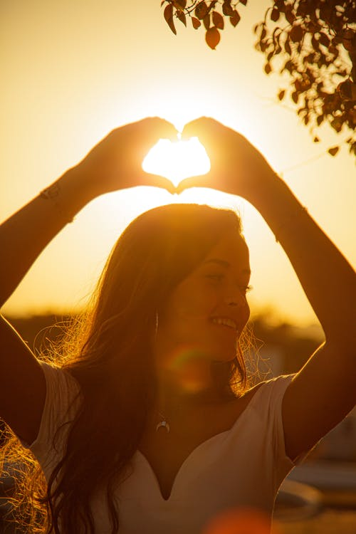 Young cheerful female making heart with hands and smiling  while looking away at sundown