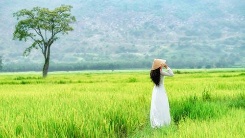 Woman in White Dress Wearing Brown Hat Standing on Green Grass Field