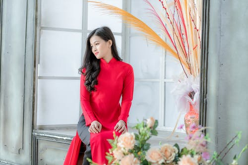 Woman in Red Long Sleeve Dress Holding Bouquet of Flowers