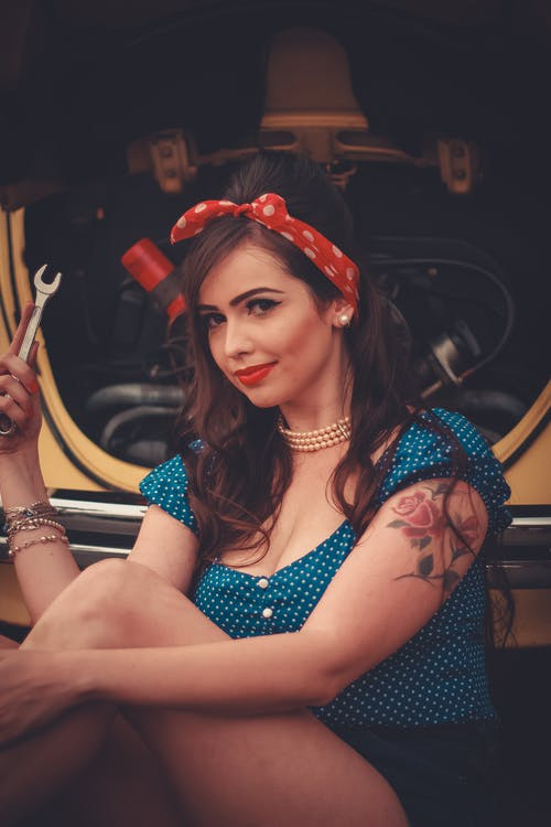 Woman in Blue and White Floral Sleeveless Top Wearing Red Flower Headband Sitting on Black Car