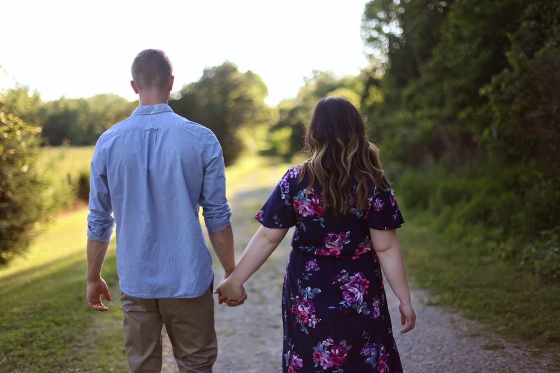 Couple Holding Hands While Walking on Path