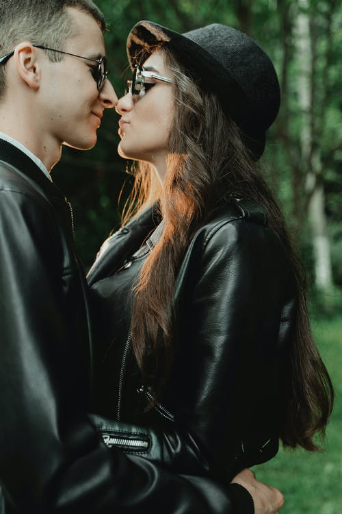 Young couple in leather jackets and sunglasses hugging