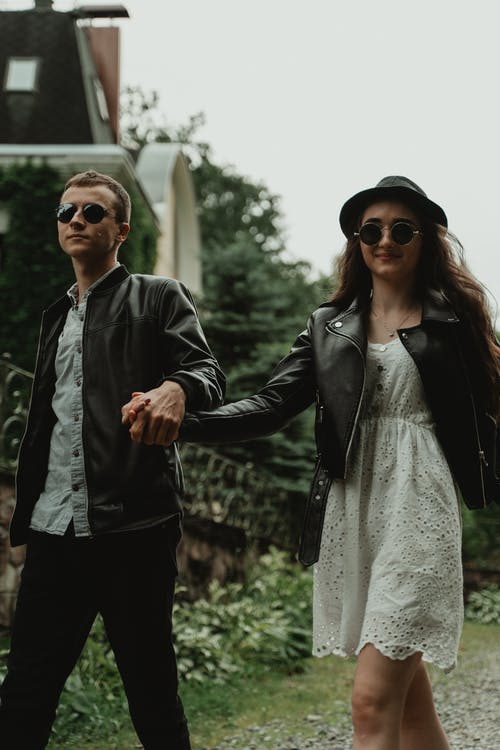 Pleasant boyfriend and charming girlfriend in sunglasses enjoying each other while walking in park at daytime