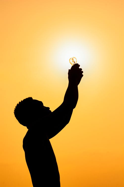 Side view of silhouette of faceless male holding light bulb against bright sun at dusk