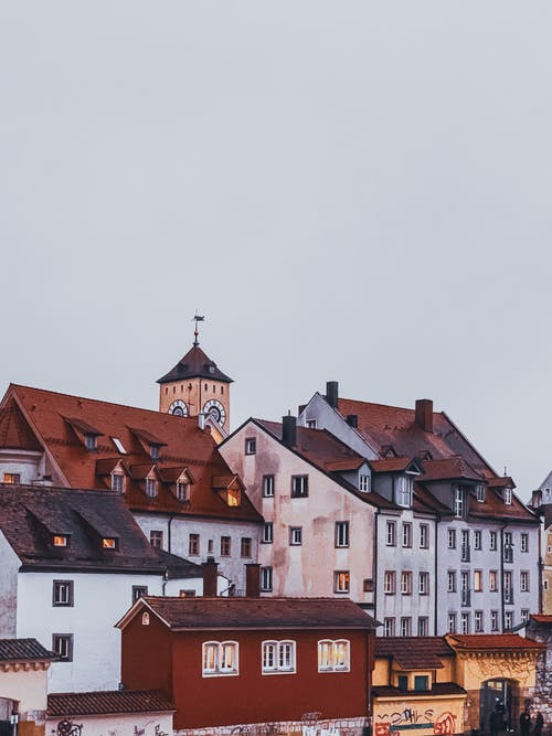 Amazing scenery of typical aged small buildings and bell tower located against cloudy sky in Regensburg