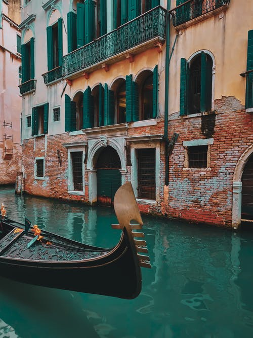 Old gondola floating on canal near traditional palazzo