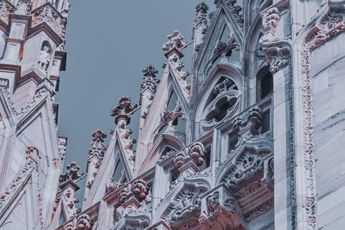 From below exterior details of Milan Cathedral with ornamental elements and sculptures under gray sky