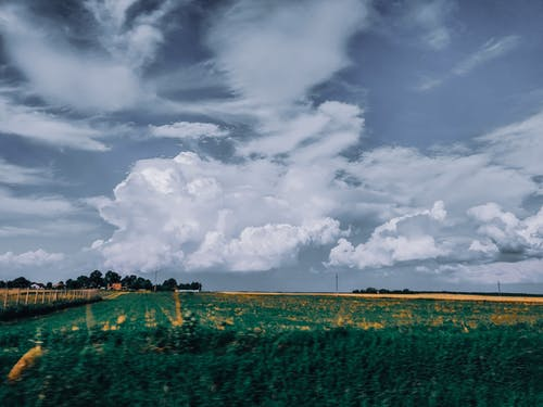 Picturesque landscape of green lush agricultural fields against amazing cloudy sky in countryside